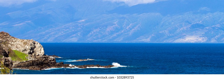 Panorama of volcanic rock and shades of blue Pacific water on the coast of Maui, Hawaii, with the island of Molokai in the background