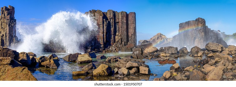 Panorama of waves breaking over basalt rock formations creating a rainbow over rockpools at Bombo Headland quarry, New South Wales coast, Australia