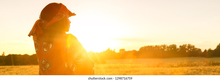 Panorama web banner African woman in traditional clothes standing, looking, hand to eyes, in field of barley or wheat crops at sunset or sunrise
