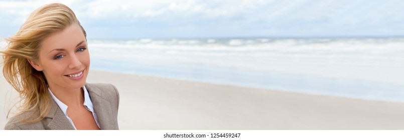 Panorama web banner of beautiful blond young woman at the beach illuminated by natural light with her hair blowing in the wind