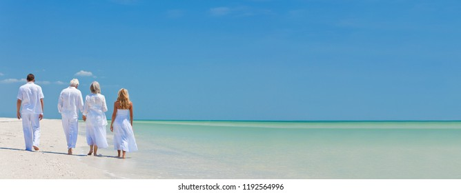 Panorama web banner rear view of four people, two seniors, couples or family generations, holding hands, walking on a tropical beach