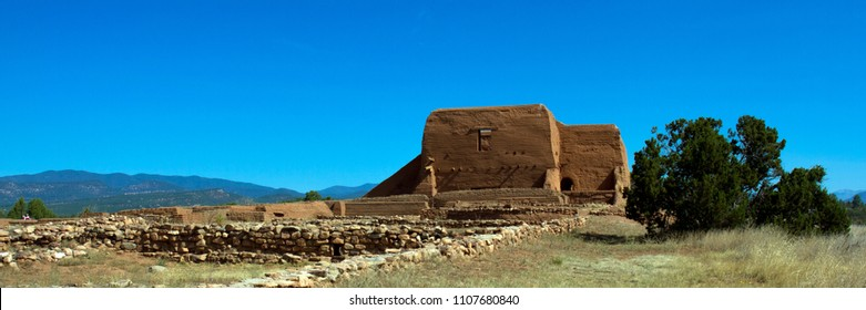 Panorama of the well-preserved walls of a Spanish mission church built in 1717 in Pecos, New Mexico, showing mountain and trees