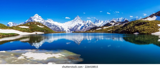 Panorama with Wetterhorn, Schreckhorn, and Finsteraarhorn peaks reflected in the waters of the Bachalpsee lake, Swiss Alps.