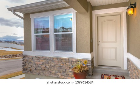 Panorama White front door and reflective window of a home against road and cloudy sky