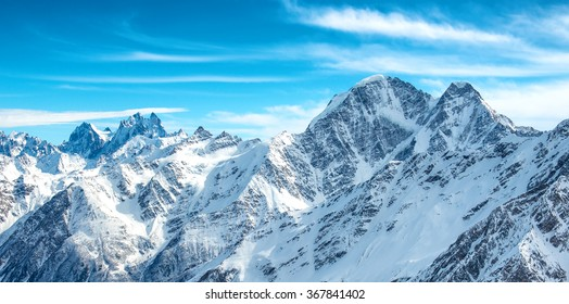Panorama of white mountains in snow. Landscape with blue peaks