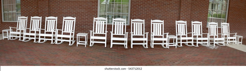 Panorama of white rocking chairs on brick porch.