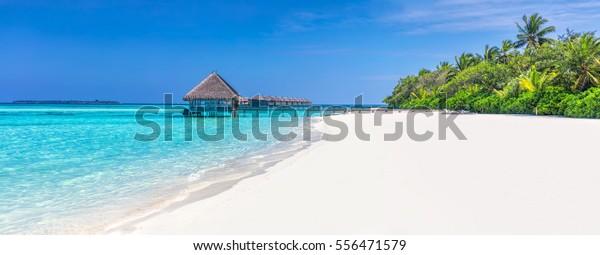 Panorama des breiten Sandstrandes auf einer tropischen Insel auf den Malediven. Kokospalmen und Wasserhaeuser am Indischen Ozean.