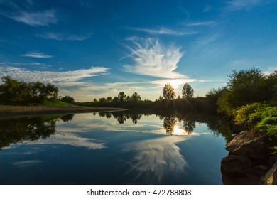 Panorama of wild river with cloudy sky reflection in autumn