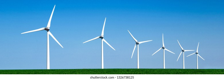 Panorama of wind turbines aligned in a green field