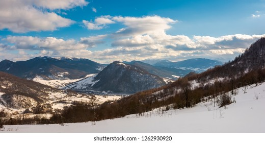 panorama of winter countryside in mountains. wonderful sunny day with gorgeous cloudscape. dark forest on the snow covered hills. village down in the distant valley. faraway ridge with snowy tops