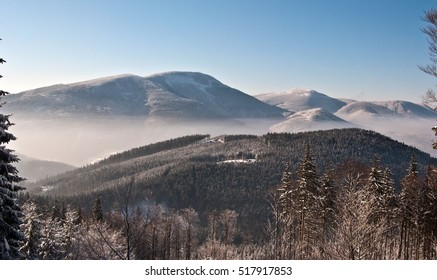 panorama of winter Moravskoslezske Beskydy mountains with misty in valley and clear sky above during hiking to Lysa hora hill