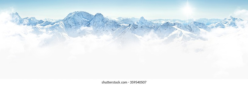 Panorama of winter mountains with clouds, bright sun and copy space