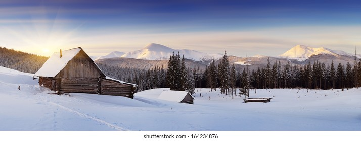 Panorama of winter mountains with houses of shepherds. Carpathians, Ukraine, Europe
