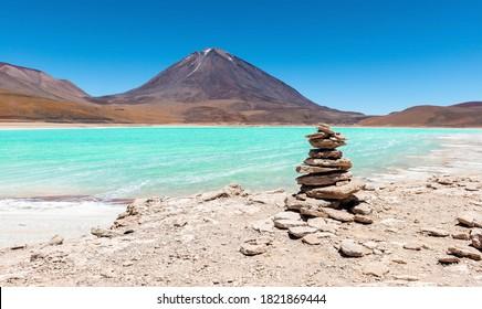 Panorama of a wish stone pyramid by the Laguna Verde (green lagoon) and the Licancabur volcano, Bolivia.