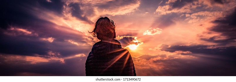 panorama woman head looking at sun breaking through clouds at sunset