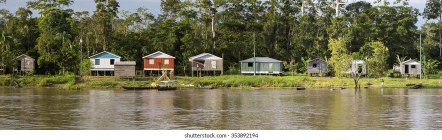 Panorama of wooden houses on stilts and Indian natives on the Amazon river bank near Manaus with the rain forest in the background. Amazonas State. Brazil 2015