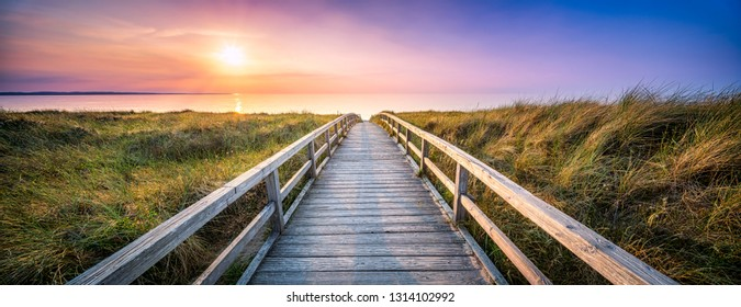 Panorama of wooden pier along the dunes during sunset
