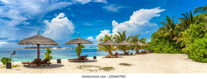 Panorama of Wooden sunbed and umbrella on tropical beach in the Maldives at summer day