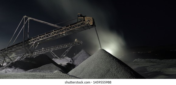Panorama of working stone crushing equipment at night at the mining factory, long exposure. Quarry mining machinery.