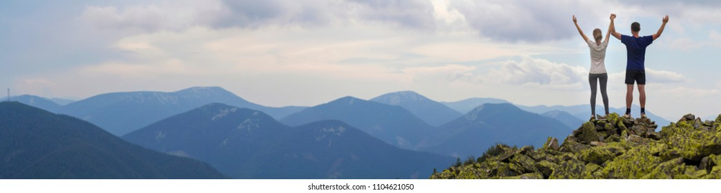 Panorama of young couple, athletic boy and slim girl standing with raised arms on rocky mountain top enjoying breathtaking summer mountain view. Tourism, success and healthy lifestyle concept.