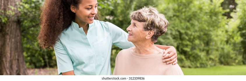 Panorama of young female afroamerican caregiver supporting elderly woman