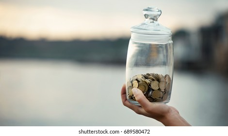 The panorama of young human hand is holding bottle money with money at the sunrise. Financial concept stability and well-being