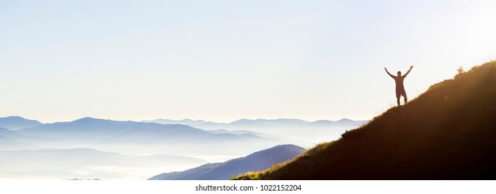 Panorama of young successful man hiker silhouette with open arms on morning foggy mountain peak. Panoramic view of tourist on mountains hill raising his hands. Successfully achieving your goal concept