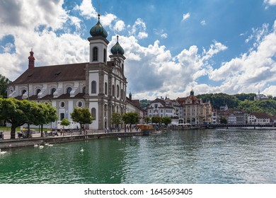 Panoramal view of the Lucerne Jesuit Church (Jesuitenkirche) on Reuss river side in old town of Lucerne with reflection in water, on a sunny summer day with blue sky cloud, Switzerland