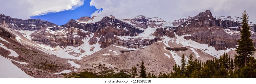 Panoramatic view of glacier and mountain valley. There is a lot of moraine and forest below the glacier. Stanley glacier in Kootenay national park in British Columbia, Canada.