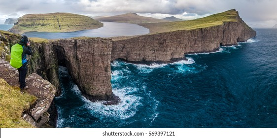 Panoramatic view into the bay with women hiker photographer, Faroes Islands