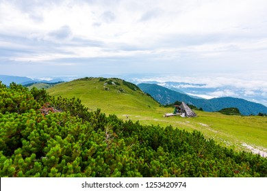 Panoramatic view to Slovenia Alps near city Kamnik. Big plateau with pasture and wooden houses. Landscape with green grass and clouds above the hill