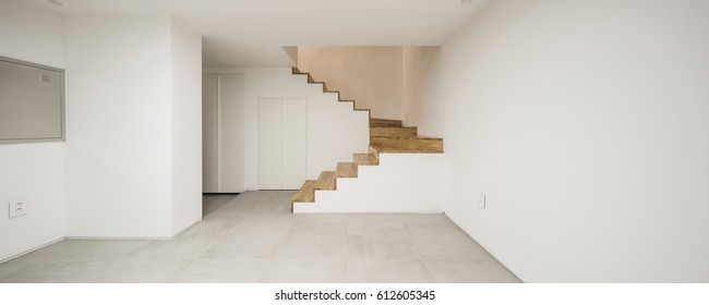 panorama(wide angle) for interior, living room with wood floor, white wall, stair, door, lighting.