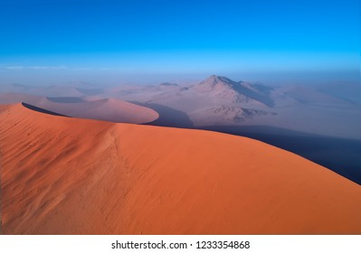 Panoramic, aerial, artistic photo of Namib dunes.  Early morning Namib desert covered in mist. Orange dunes of Namib from above. Desert landscape. Sunrise in Namib-Naukluft  desert. Traveling Namibia.