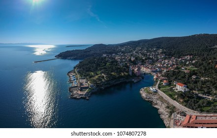 Panoramic aerial photo of the village of Veli Losinj in the Croatian island. View towards the port or marina of the village. Beautiful colorful houses and church are seen.