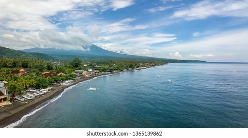 Panoramic aerial view of Amed beach in Bali, Indonesia. Traditional fishing boats called jukung on the black sand beach and Mount Agung volcano in the background, partially covered by clouds.