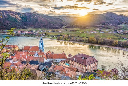 Panoramic aerial view of beautiful Wachau Valley with the historic town of Durnstein and famous Danube river in beautiful golden evening light at sunset, Lower Austria region, Austria