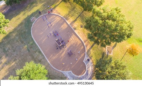 Panoramic aerial view a big kid games playground at Harwin Park in Houston, Texas in fall. Elevated view slides and swings in the park surrounded green trees. Children outdoor play, recreation concept