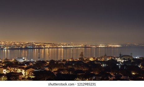 Panoramic aerial view of Cascais Bay with Rei Cristo statue in background and Ponte 25 Abril, Portugal in far background