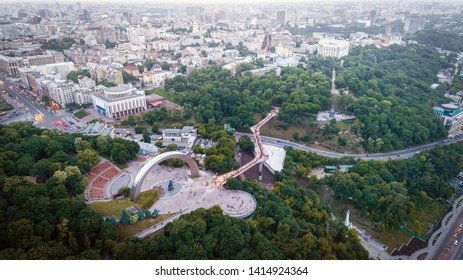 Panoramic aerial view of the city center of Kiev at night near the Arch of Friendship of Peoples with a new glass bridge from Khreschaty Park to Vladimirskaya Gorka Park.