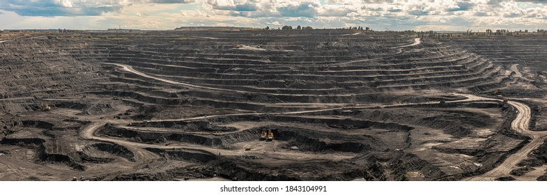 Panoramic aerial view of coal mine. Open pit mine industry, big yellow mining truck for coal quarry. Open coal mining anthracite mining. Pit on coal mining by open way. Rock loading in trucks