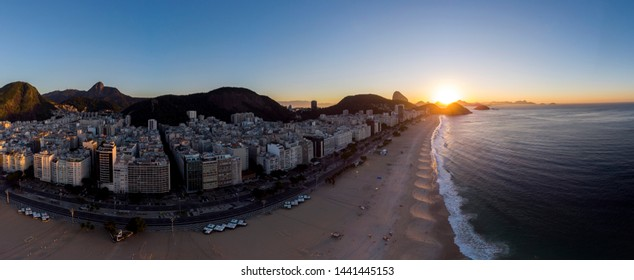 Panoramic aerial view of Copacabana beach and neighbourhood in Rio de Janeiro with the Sugarloaf mountain in the background against a colourful blue sky at sunrise