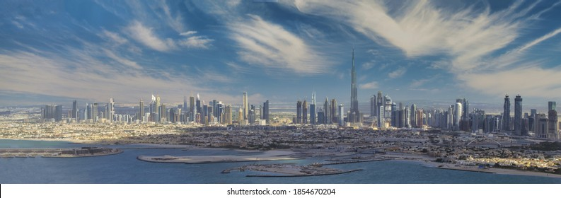 Panoramic aerial view of Downtown Dubai skyline at sunset, United Arab Emirates from helicopter.