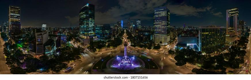 Vista aérea panorámica de la famosa avenida Reforma llena de árboles y enormes edificios de oficinas iluminados por las luces nocturnas de la ciudad