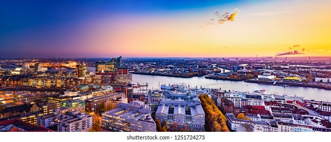 """Panoramic aerial view of the harbor district, the concert hall """"Elbphilharmonie"""" and downtown Hamburg, Germany, at dusk."""