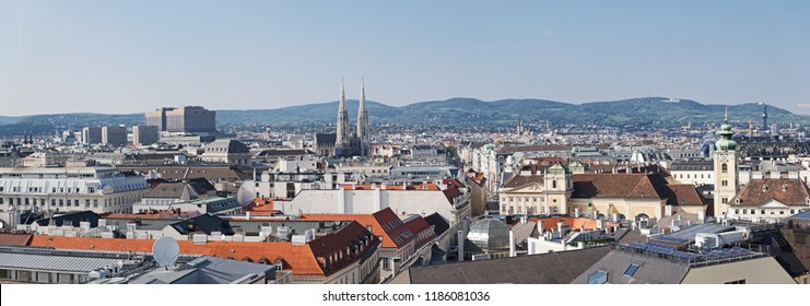 Panoramic aerial view from the historic old town of Vienna over the western part of the city with some famous landmarks and Vienna Woods in the background.