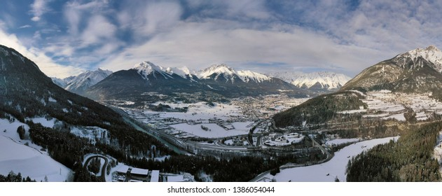 Panoramic aerial view of idyllic winter wonderland mountain Alps on a sunny day with blue sky. Imst, Austria.