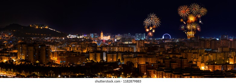 Panoramic aerial view to illuminated Malaga city at night and fireworks blowing in the sky