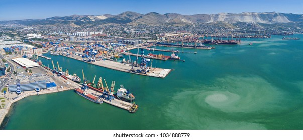 Panoramic aerial view of the international sea port of Novorossiysk. Port cranes, containers and cargo ships.