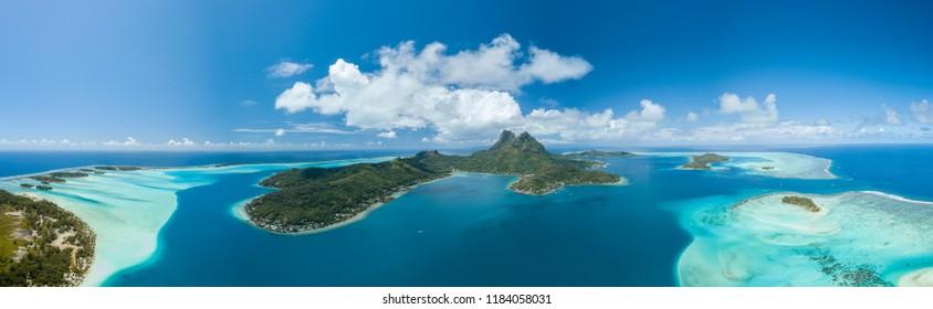 Panoramic aerial view of luxury overwater villas with palm trees, blue lagoon, white sandy beach and Otemanu mountain at Bora Bora island, Tahiti, French Polynesia (Bora Bora Aerial)