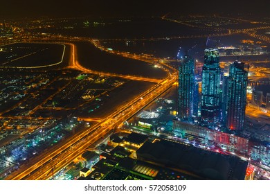 Panoramic aerial view on downtown of Dubai with modern high skyscrapers at night. Architecture of future with bright lights and roads. Famous tourist destination